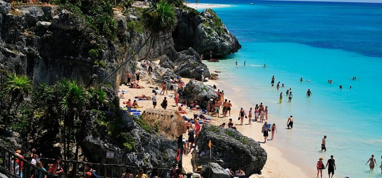 Travelers to Tulum, Mexico walking along the beach between the rocky cliff and bright blue waters