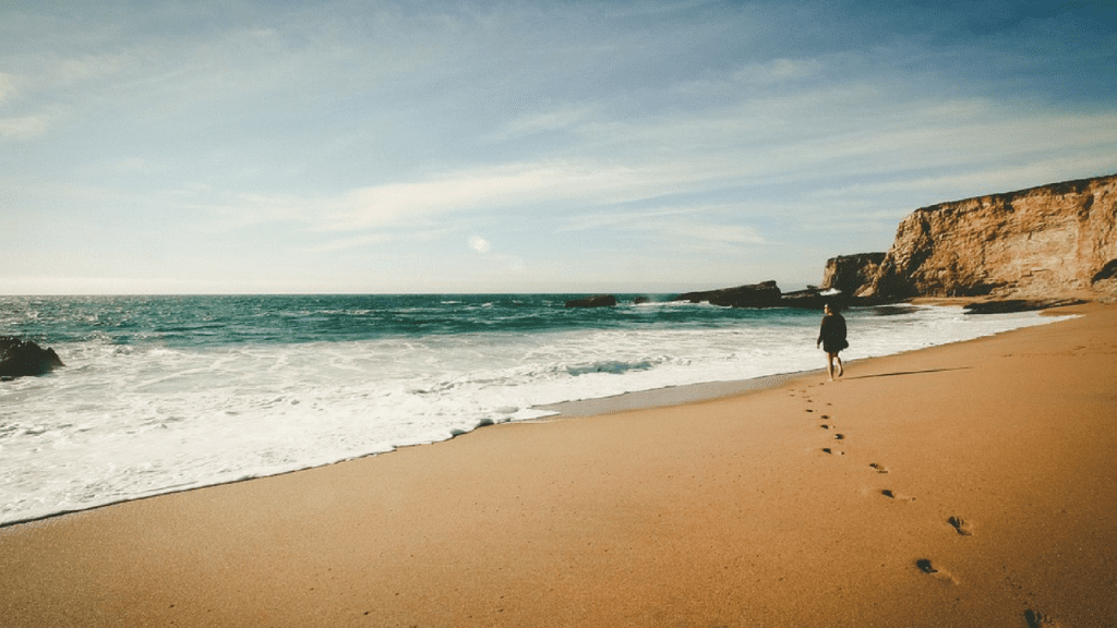 beach in portugal iwth a person standing at the waters edge. there are footprints leading to the person and cliffs in the background