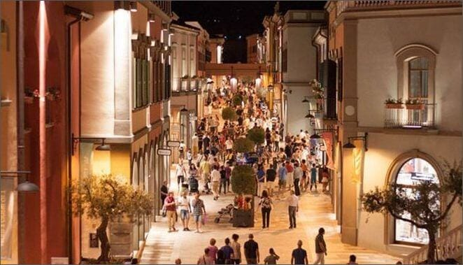 an italy street at night with people shopping